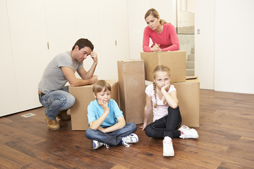A young family sitting amongst packing boxes. They look dejected.