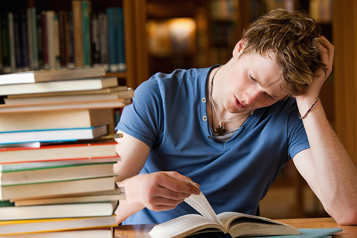 Tired, stressed young man with a pile of books.