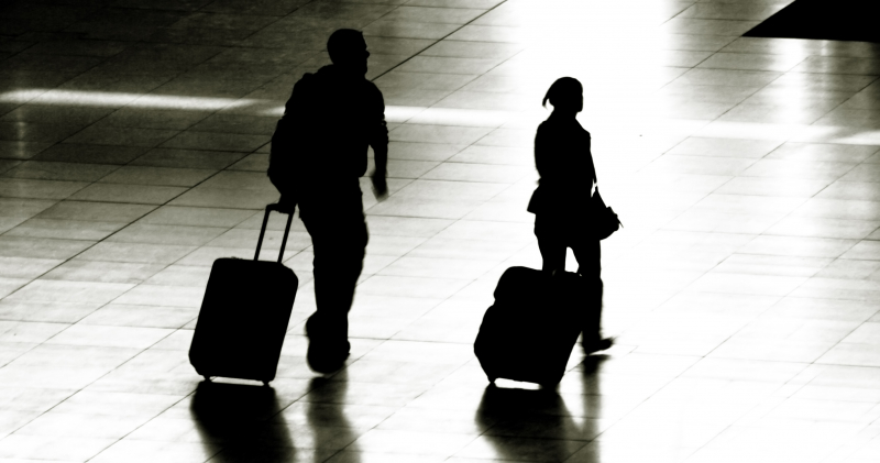 A man and a girl walking, each with a suitcase.