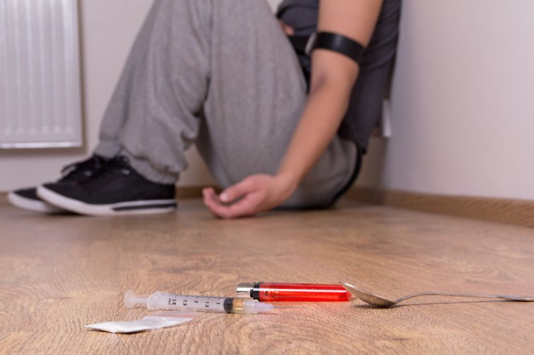A boy sitting against a wall with drug paraphernalia on the floor.